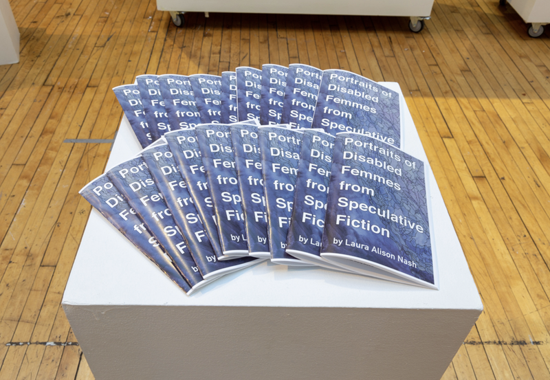 "Several copies of a booklet spread on top of a white pedestal, which stands on a wooden floor. The booklet is titled ""Portraits of Disabled Femmes from Speculative Fiction by Laura Alison Nash,"" in white lettering on a purplish cover."